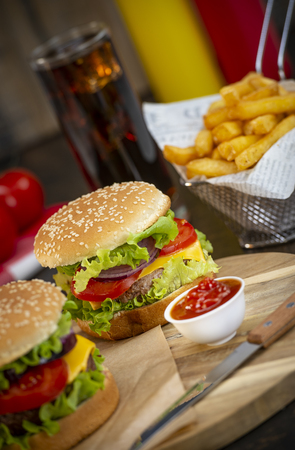 Burger with French fries cutlet with cheese and tomato, France Stock Photo - 117720224