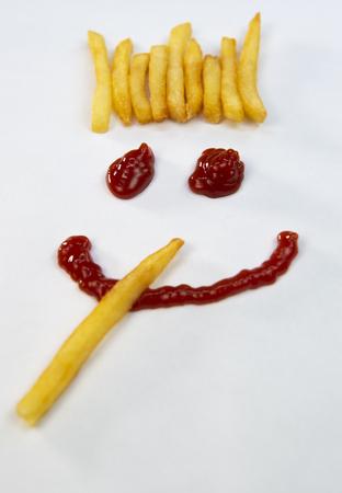 Capelli di patate, patatine fritte e una faccia con un sorriso da ketchup isolato su sfondo bianco