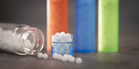 Modern Color homeopathic pills in plastic container on black background, France Stock Photo