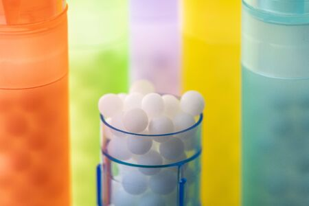 Modern Color homeopathic pills in plastic container on black background, France 免版税图像