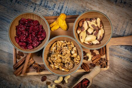 Mixed nuts and dried fruits in wooden bowl on wood background, copy space