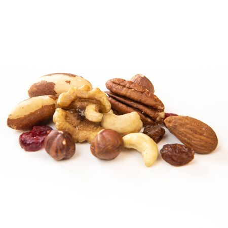 Mixed nuts and dried fruits in wooden bowl on white background, copy space