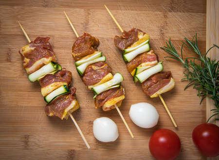 Raw lamb skewers with zucchini slices on wood Standard-Bild