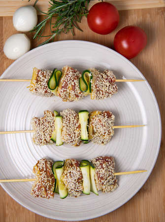 Raw lamb skewers with zucchini slices and sesame seeds