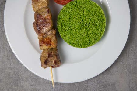 Lamb brochette marinated in spices, green semolina Standard-Bild