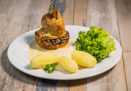 Chicken gigolette recipe with mushrooms accompanied by turned potatoes and salad, creamy sauce Standard-Bild