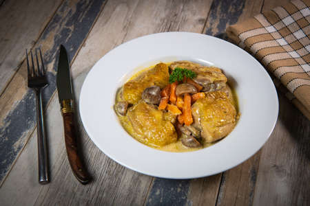 Recipe for chicken fricassee in white wine, with a carrot and mushroom planter Standard-Bild