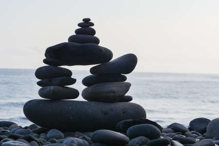 Stone piles made along a beach and the sea in the background