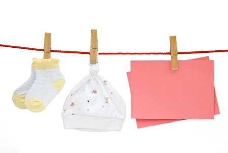 baby socks and cap and blank note hanging