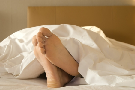 feet of a man lying down on bed photo