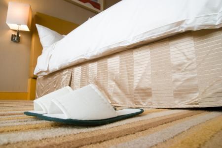hospedaje: zapatillas y una cama en una habitación de hotel