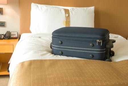 suitcase on bed inside a hotel room Standard-Bild