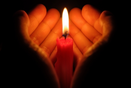 hands holding a burning candle in dark