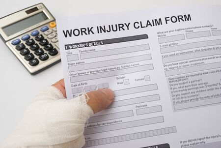 hurted hand holding a work injury claim form Stock Photo - 18622616