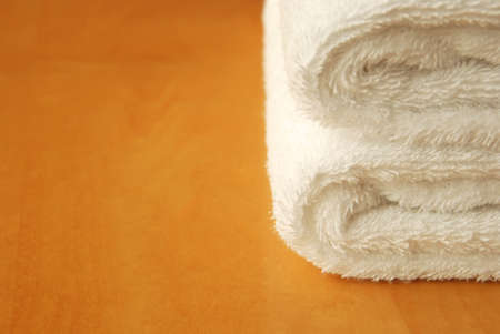 orange washcloth: white towel on wooden panel with copy space Stock Photo