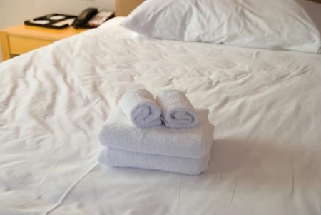 hospedaje: toallas en la cama en una habitación de hotel Foto de archivo
