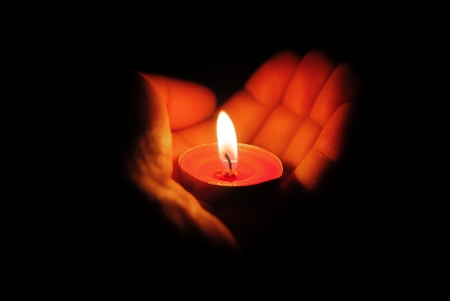 left hand holding a burning candle in dark photo