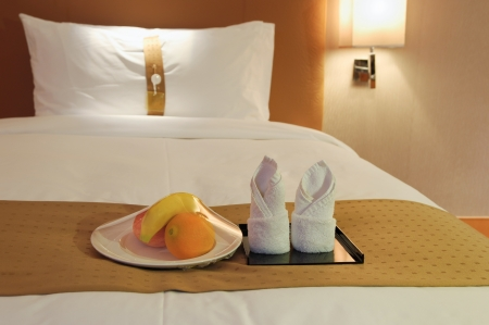 orange washcloth: towels and fruit on bed in a hotel room