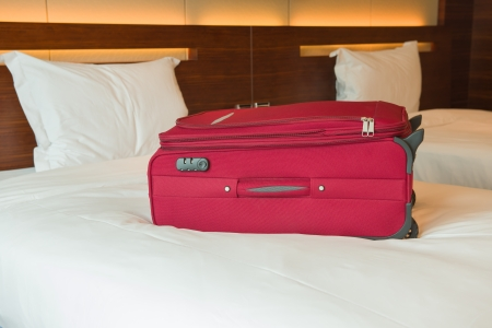 red suitcase on bed inside a hotel room