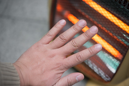 heating up a hand in front of an electric heater Stock Photo
