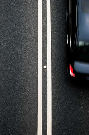 vertical divider: double white lines divider on blacktop with a car passing