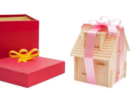 house wrapped with ribbon besides a present box with clipping path photo