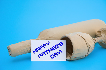 card of HAPPY FATHERS DAY and wine and cup with copy space