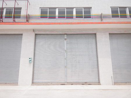 blank metal shutter doors on commercial shop front, symmetrical composition photo