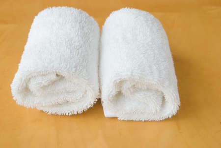 two rolls of white towel roll on wooden panel