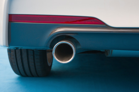 exhaust pipe of a white car on blue carpet photo