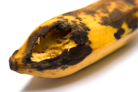 ripe banana bited by insect on white close up photo