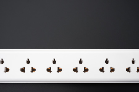 mains: multi sockets power extension on black close up Stock Photo