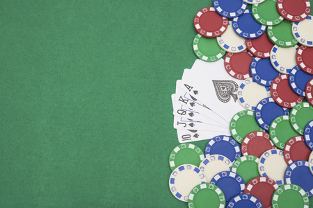 pokers: 10 to Ace spade straight flush of pokers and lots of chips on casino table with copy space