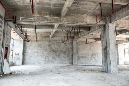 mezzanine: Empty industrial loft in an architectural background with bare cement walls, floors and pillars supporting a mezzanine