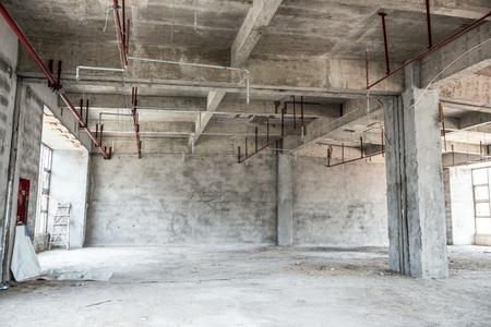 locales comerciales: Loft industrial vacío en un fondo arquitectónico con desnudos de cemento paredes, suelos y pilares que sostienen un entrepiso