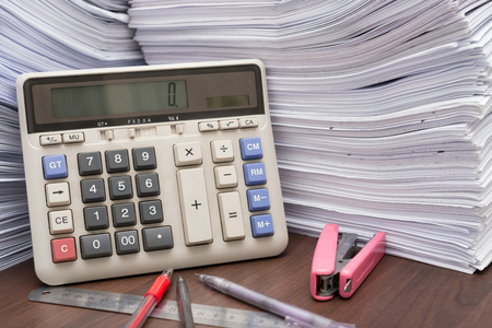 Pile of documents on desk stack up high with calculator, pen and ruler on office desk photo