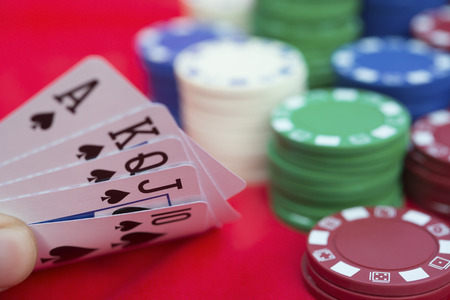 pokers: poker player holding 10 to Ace spade straight flush of pokers beside lots of chips Stock Photo