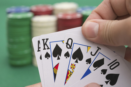 poker player: poker player holding 10 to King spade straight flush of pokers, A spade  is coming