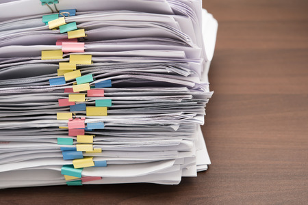 to pile up: Pile of documents with colorful clips on desk stack up