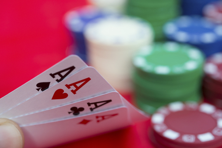 pokers: poker player holding 4 Ace spade straight flush of pokers beside lots of chips