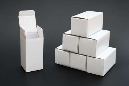 several: several white boxes with one opened and ther other closed on black Stock Photo
