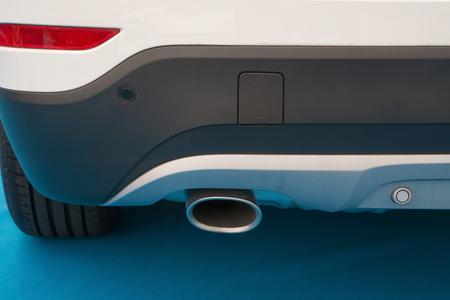 exhaust pipe: exhaust pipe of a white car on blue carpet