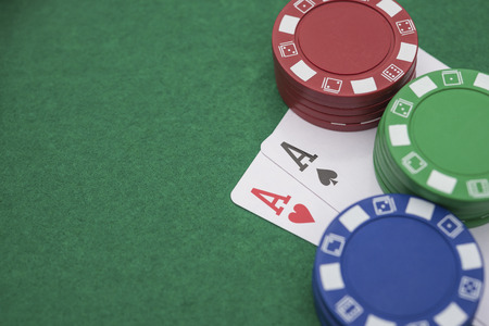 pokers: two Ace of pokers beside lots of chips on casino table