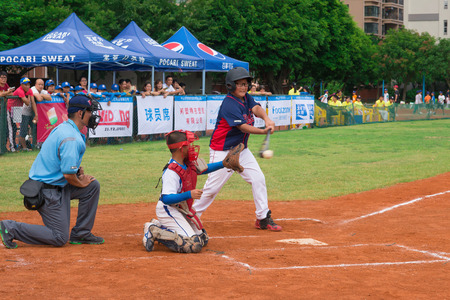 baseman: ZHONGSHAN, GUANGDONG - July 23:batter of team WenZhou XinTianYuan Primary School hit the ball during a match of 2015 National Baseball Championship. Group A of Panda Cup against Zhongshan TongMao Primary School on July 23, 2015.