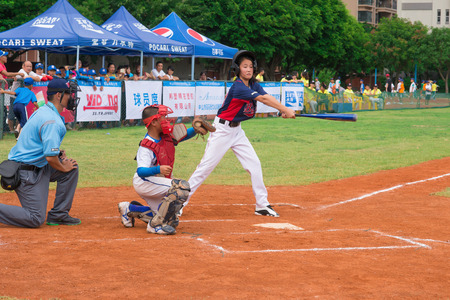 baseman: ZHONGSHAN, GUANGDONG - July 23:batter of team WenZhou XinTianYuan Primary School missed the ball during a match of 2015 National Baseball Championship. Group A of Panda Cup against Zhongshan TongMao Primary School on July 23, 2015. Editorial