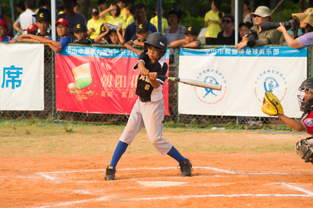 baseman: ZHONGSHAN PANDA CUP, ZHONGSHAN, GUANGDONG - August 4:batter of team WuXi Experimental Primary School about to hit the ball during a match of 2015 National Baseball Championship of Panda Cup against TaiWan Zhanghua Dongshan Primary School on August 4, 2015