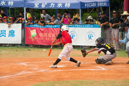 baseman: ZHONGSHAN PANDA CUP, ZHONGSHAN, GUANGDONG - August 4:batter of team TaiWan Zhanghua Dongshan Primary School hit the ball during a match of 2015 National Baseball Championship of Panda Cup against WuXi Experimental Primary School on August 4, 2015.