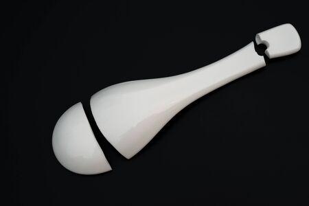 splinter: top view of a broken porcelain spoon on a black background