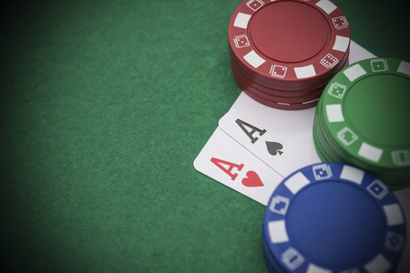 poker: two Ace of pokers beside lots of chips on casino table