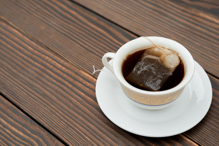 teabag: cup of tea with teabag on a wooden background